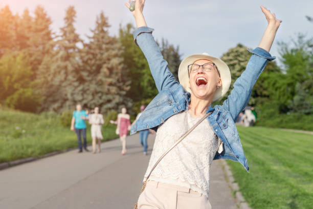 happy young caucasian bald woman in hat and casual clothes enjoying life after surviving breast cancer. portrait of beautiful hairless girl smiling during walk at city park after curing disease - sopravvivenza foto e immagini stock