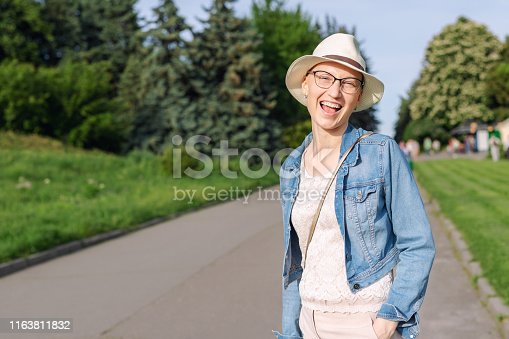 469949126 istock photo Happy young caucasian bald woman in hat and casual clothes enjoying life after surviving breast cancer. Portrait of beautiful hairless girl smiling during walk at city park after curing disease 1163811832