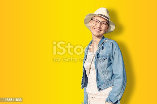 469949126 istock photo Happy young caucasian bald woman in hat and casual clothes enjoying life after surviving breast cancer. Portrait of beautiful hairless girl smiling isolated on golden yellow background 1163811833