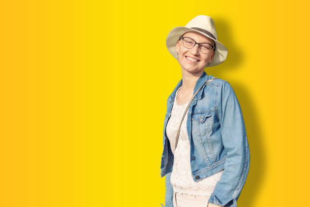 happy young caucasian bald woman in hat and casual clothes enjoying life after surviving breast cancer. portrait of beautiful hairless girl smiling isolated on golden yellow background - nakrycie głowy zdjęcia i obrazy z banku zdjęć