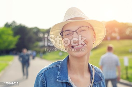 Happy young caucasian bald woman in hat and casual clothes enjoying life after surviving breast cancer. Portrait of beautiful hairless girl smiling during walk at city park after curing disease.