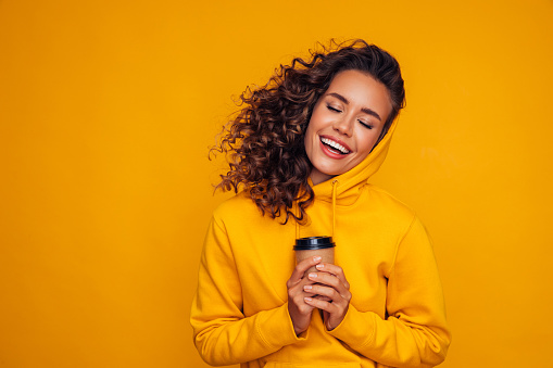 Happy young cheerful girl laughing and holding cup of coffee on colored yellow background