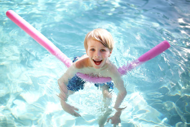 Happy Young Child Floating in Swimming Pool stock photo