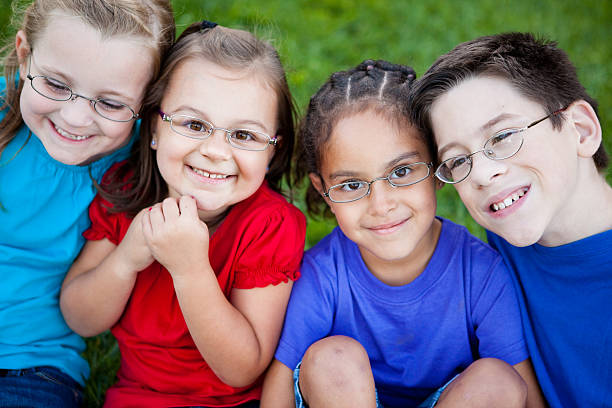 Happy Young Children with Glasses Smiling Outside stock photo