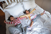 High angle view of excited young Chinese brother and sister laying spreadeagled on messy guest bed.