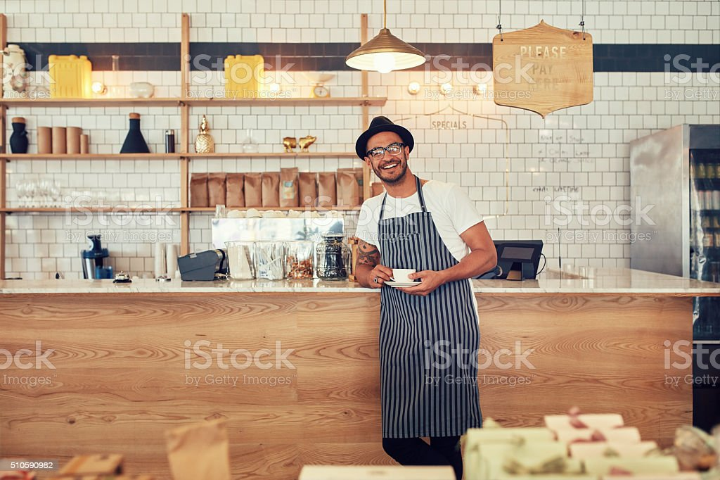 Happy young coffee shop owner stock photo