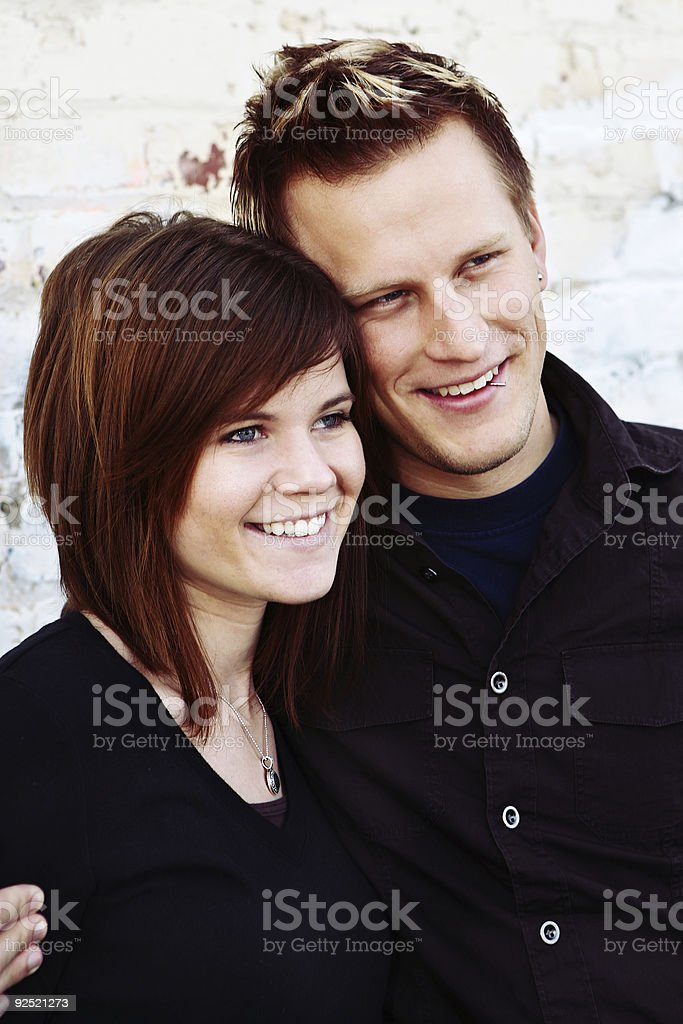 Happy Young Couple Against Brick Wall royalty-free stock photo