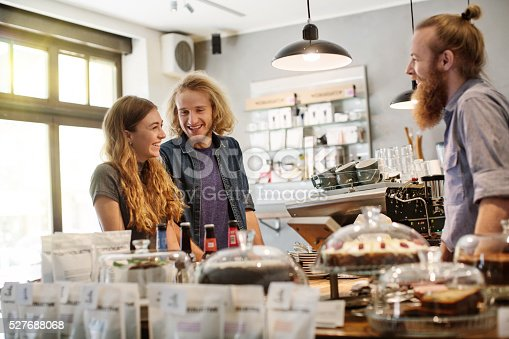 597640822 istock photo Happy young couple at cafe counter 527688068