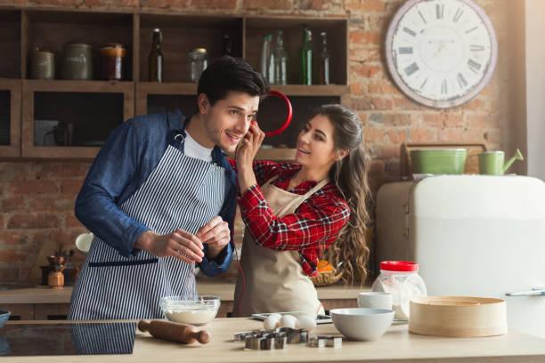 glückliches junges paar backen im loft küche - musik kuchen stock-fotos und bilder