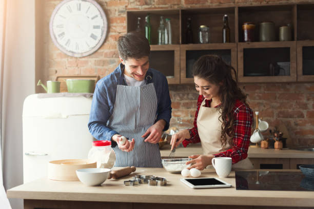 Happy young couple baking in loft kitchen Happy young woman and man baking pie in loft kitchen. Young family cooking at home, using digital tablet. Mockup for recipe making a cake stock pictures, royalty-free photos & images