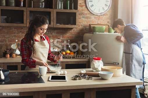 istock Happy young couple baking in loft kitchen 997690000