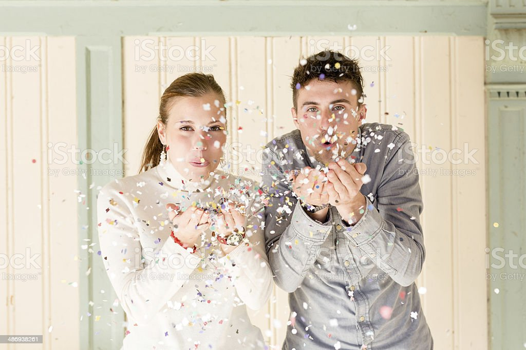 Happy young couple blowing confetti royalty-free stock photo