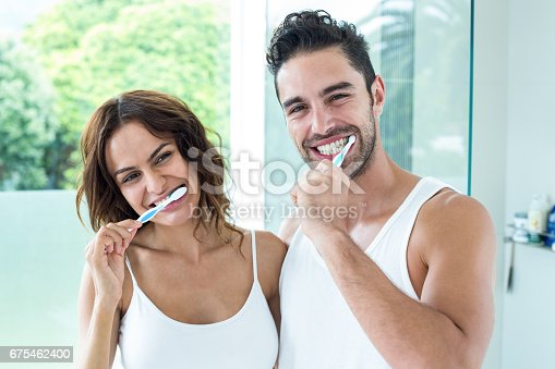 675462768istockphoto Happy young couple brushing teeth 675462400