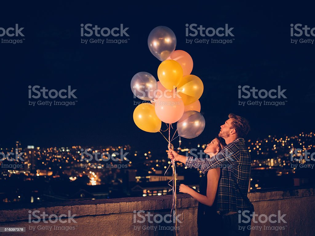 Happy young couple celebrates with colourful ballons on the rooftop stock photo