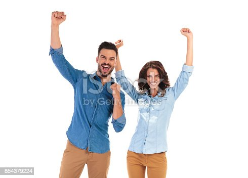 854381886 istock photo happy young couple celebrating success with hands up 854379224