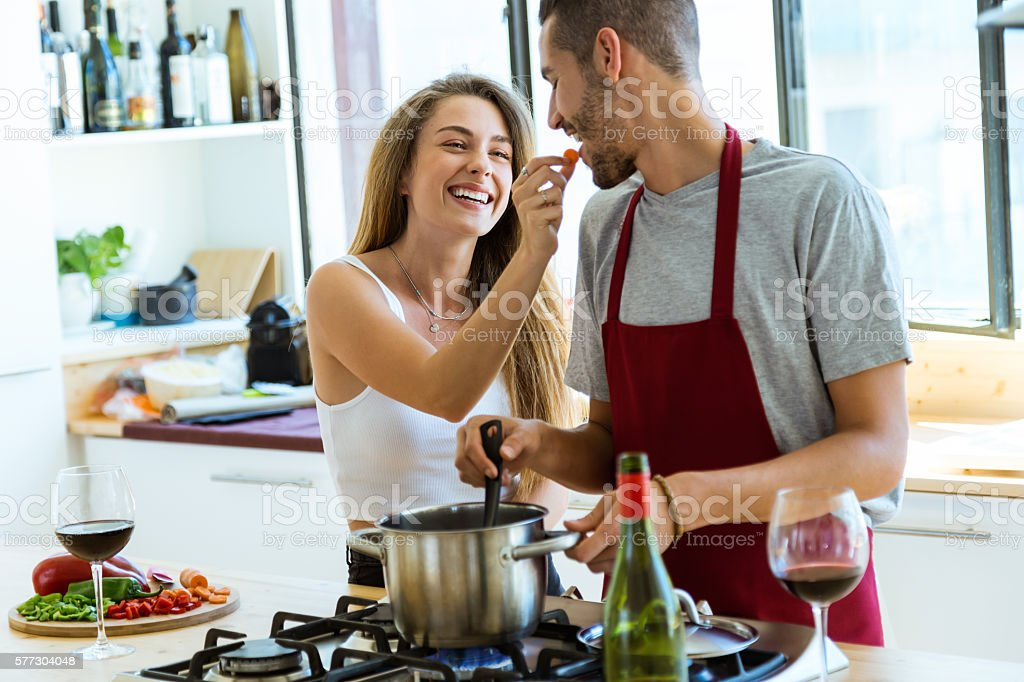 Happy young couple cooking together in the kitchen at home. stock photo