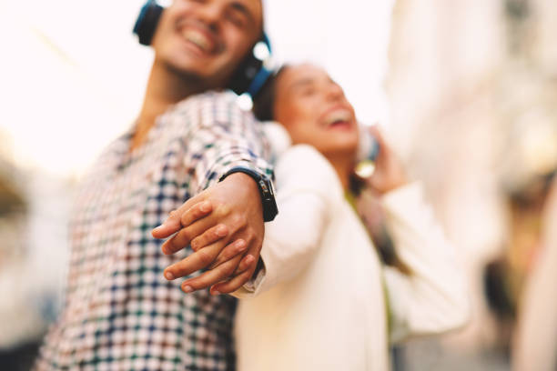 Happy young couple dancing on the street and listening to music through headphones and holding hands. Selective focus on hadns. stock photo