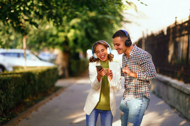 Happy young couple dancing on the street and listening to music through headphones stock photo