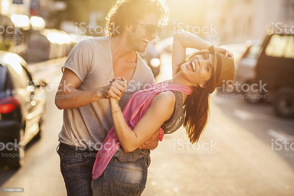 Happy young couple dancing on the street stock photo