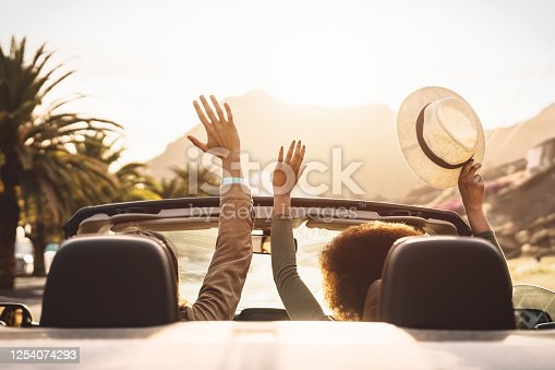 1030408008 istock photo Happy young couple doing road trip in tropical city - Travel people having fun driving in trendy convertible car discovering new places - Relationship and youth vacation lifestyle concept 1254074293