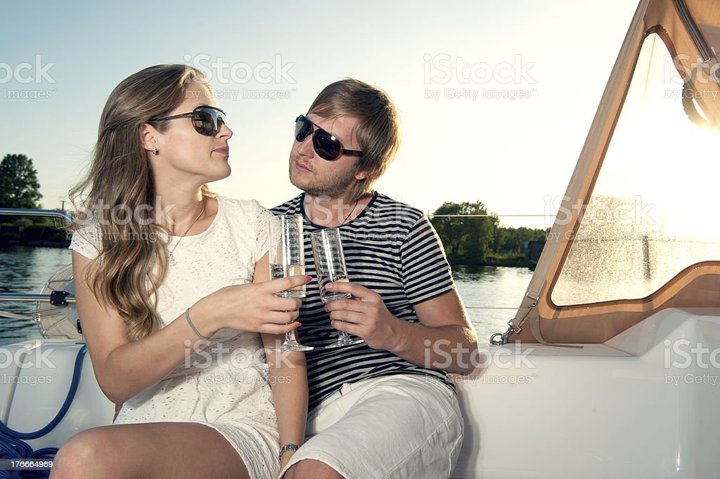 Happy young couple drinking champagne on yacht royalty-free stock photo