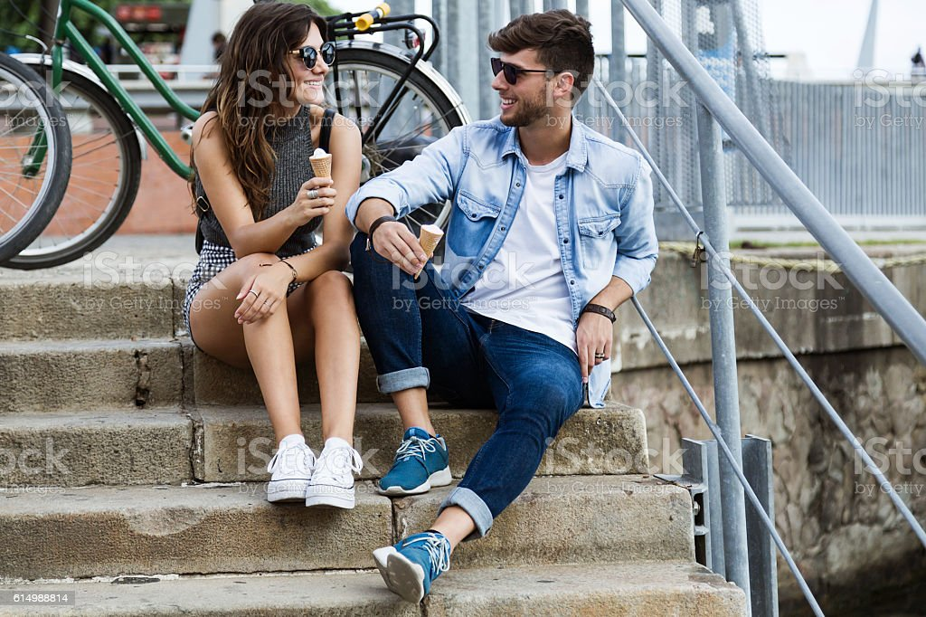 Happy young couple eating ice cream in the street. stock photo