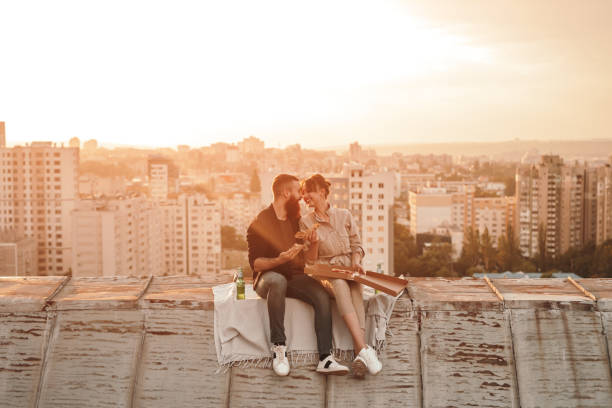 Happy young couple eating pizza on roof stock photo