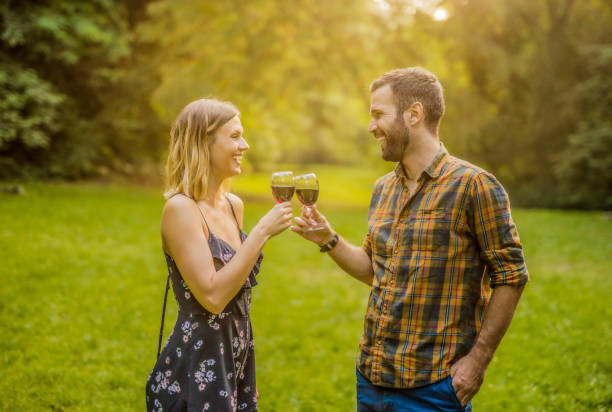 Happy young couple enjoying wine together in nature. stock photo