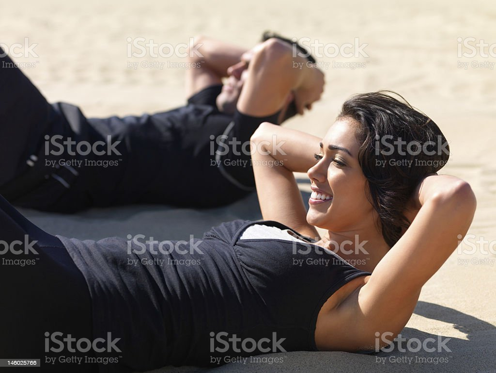 Happy young couple exercising on beach royalty-free stock photo