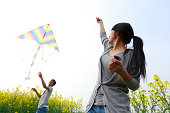 happy young asian couple flying kite in the spring field