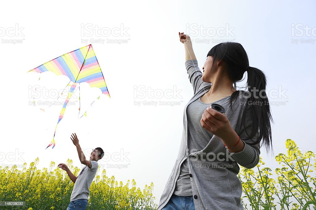 happy young couple flying kite stock photo
