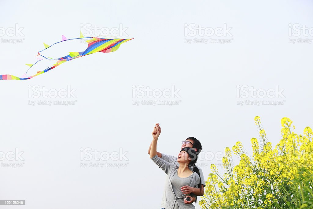 happy young couple flying kite royalty-free stock photo