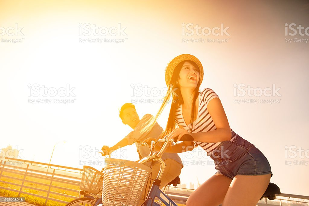 Happy young couple going for  bicycle ride stock photo