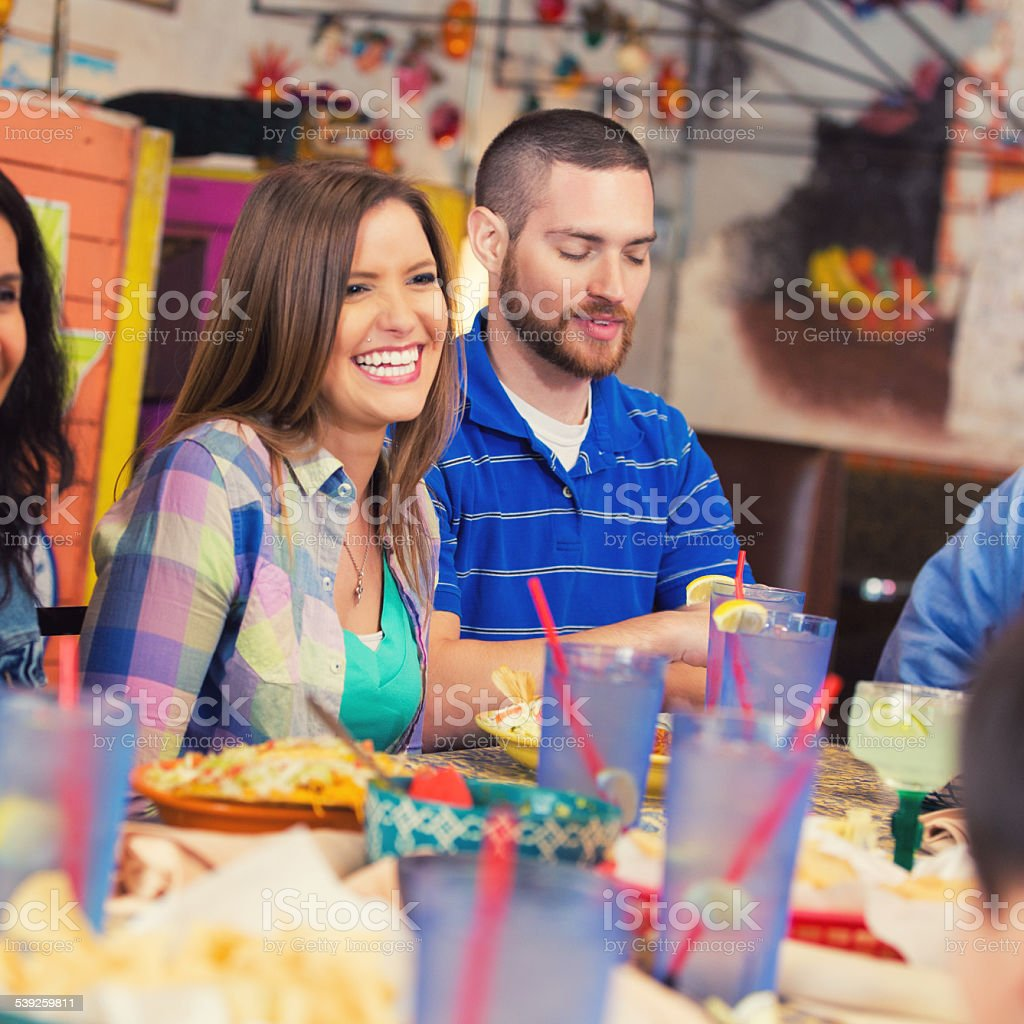 Happy young couple having dinner with friends in Tex-Mex restaurant stock photo