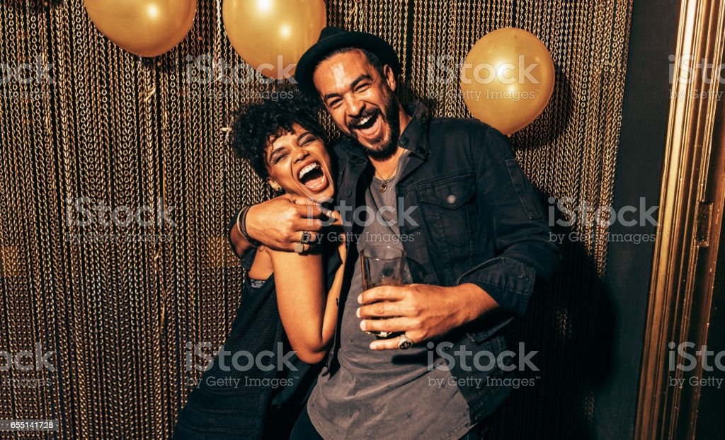 Happy young couple having fun at disco stock photo