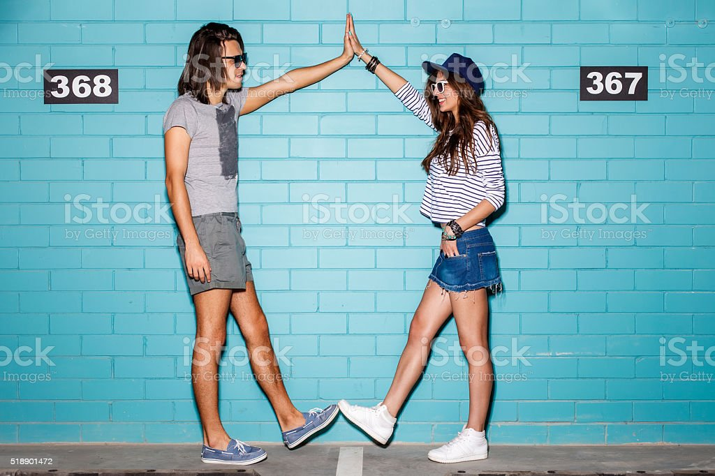 happy young couple having fun in front of blue wall stock photo