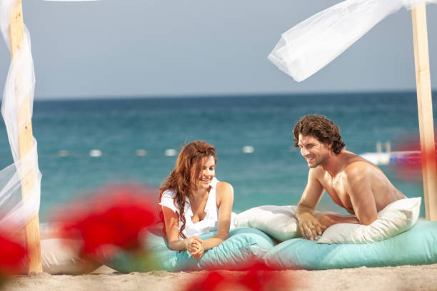 Happy young couple having fun in wooden gazebo at beach on sunny day stock photo