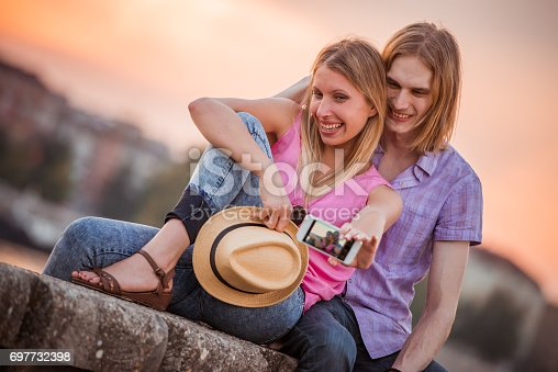 1069131934 istock photo Happy young couple having fun outdoors and smiling 697732398