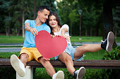 istock Happy young couple holding a big red heart 1266861926