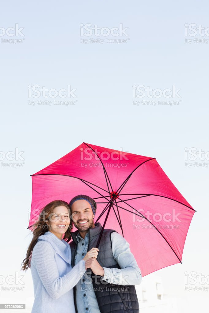 Happy young couple holding pink umbrella royalty-free stock photo