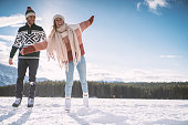 Happy young couple ice skating hand in hand on frozen lake enjoying winter fun