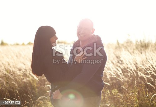 istock Happy young couple in a field 499737173