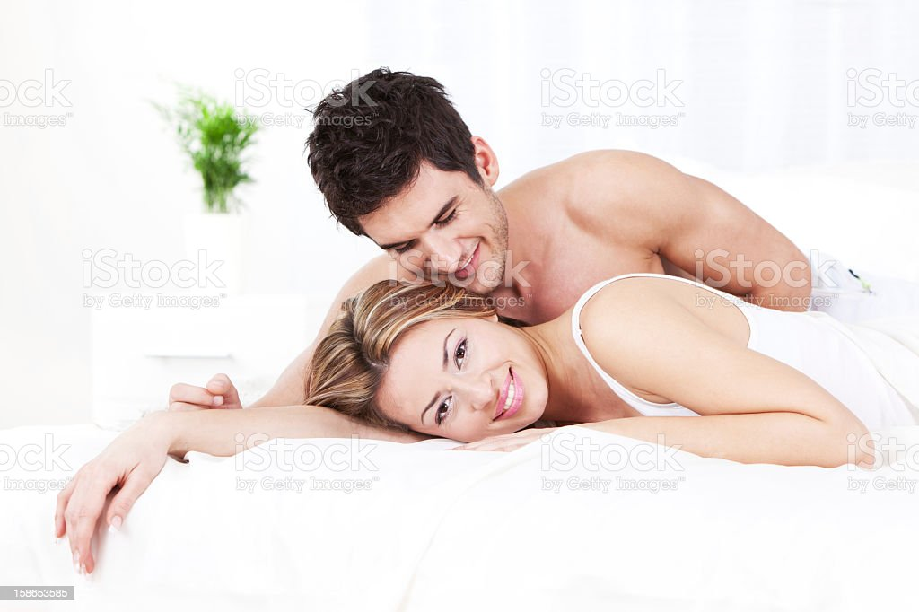 Happy young couple in bed Beautiful young couple lying down in bed, smiling and looking at camera. 20-24 Years Stock Photo
