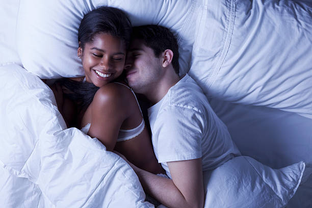 """Happy Young Couple in Bed """"Photo of an attractive young mixed race couple, lying in bed as husband playfully invades his wife's side of the bed."""" real couples making love stock pictures, royalty-free photos & images"""