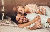 幸せな若いカップルはベッド