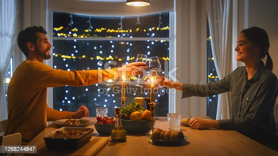 istock Happy Young Couple in Love Have Romantic Dinner, Toasting Each other with Glasses of Wine, Eating Tasty Meal in the Kitchen, Celebrating, Talking. Beautiful Lovely Husband and Wife Have Romantic Time 1268244847