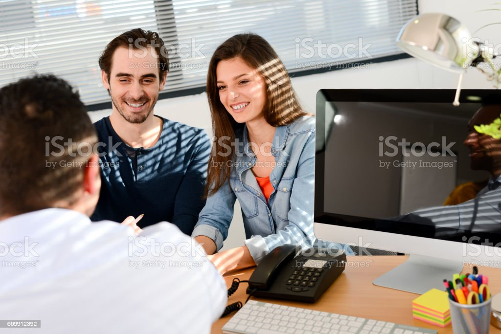 happy young couple in office with businessman on business buying agreement contract signature - Photo