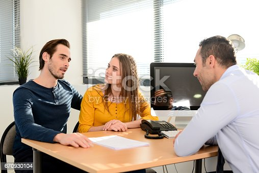 istock happy young couple in office with businessman on business buying agreement contract signature 670930104