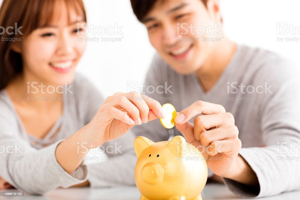 Happy young Couple Inserting Coin In Piggybank stock photo