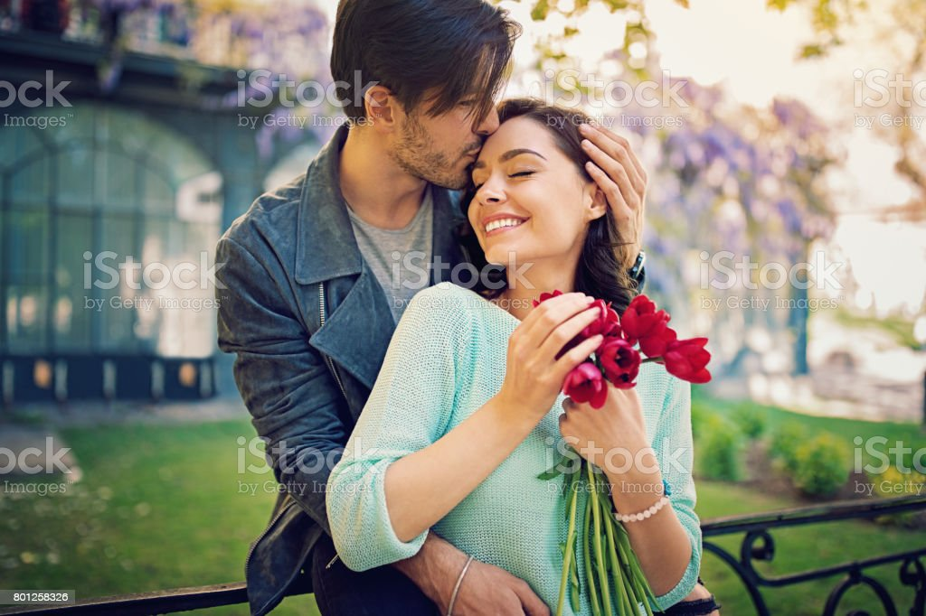 Happy, young couple is hugging and kissing on the fence stock photo